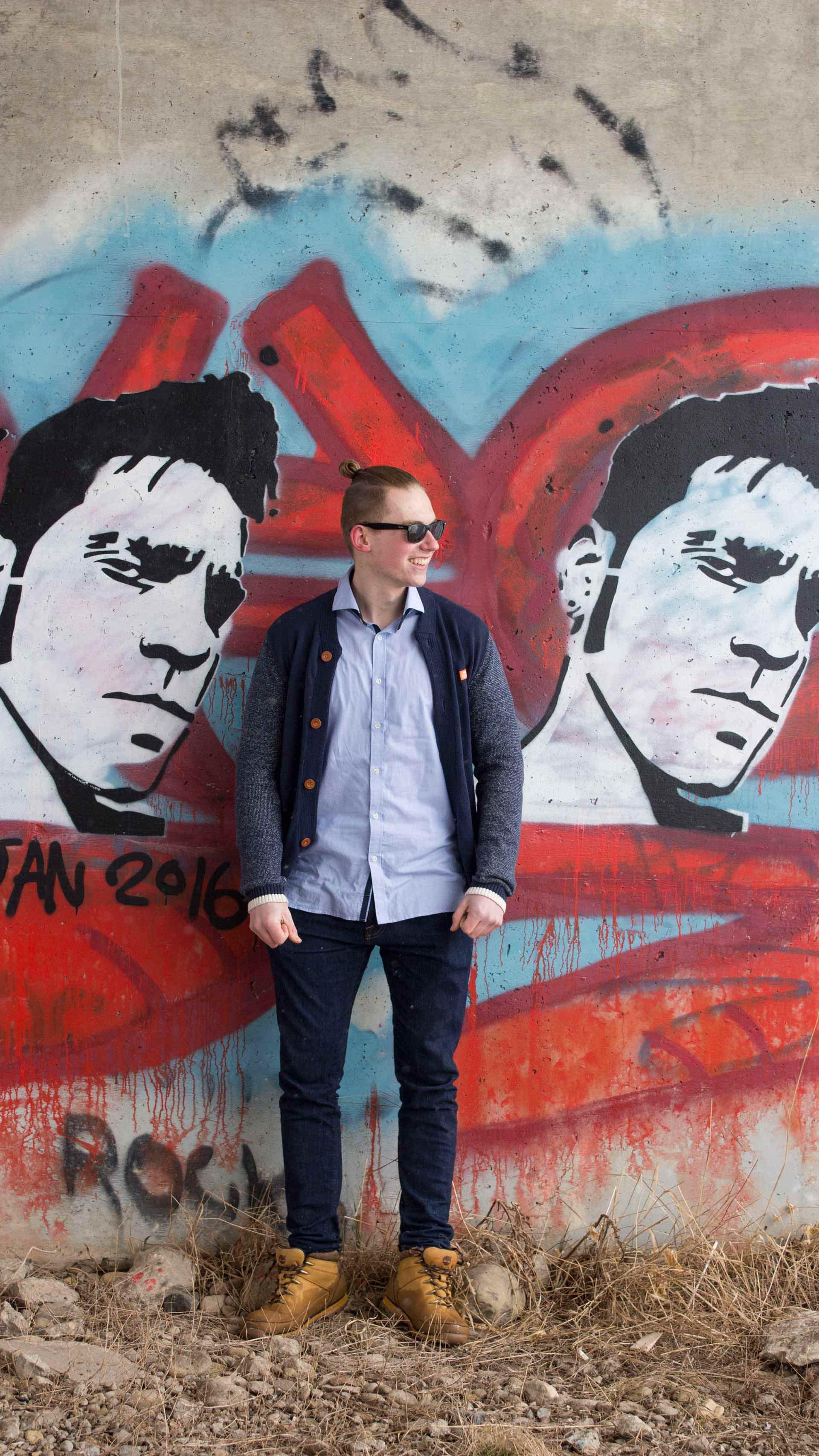 Patrick standing in between graffiti art