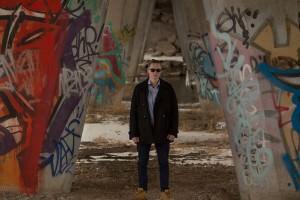 Patrick standing near graffiti