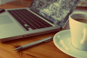 Laptop with coffee cup and pen
